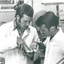 Image of Bill Hirsch, dental technician with one of his counterparts in dental lab.