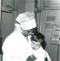 Image of Brenda Thorpe holding a pediatric patient prior to surgery.