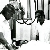 Image of Dr. Al Schmitz in the X-ray room with his counterpart and patient.