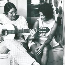 Image of Agnes Fee and Susan Agnew relaxing playing the guitar.