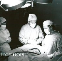 Image of Dr. Ulpio Miranda, Dr. Jack Mahoney and OR nurse Barbara Wright in OR.