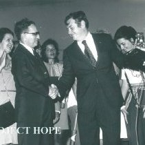 Image of Dr William B Walsh shaking hands and Olga Verduzco behind to right.