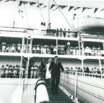 Image of Dr and Mrs William B Walsh walking down the gangway upon arrival in Maceio.