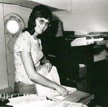 Image of Rita Daniels, Secretary, in her office before her surgery.