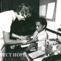 Image of Susan Willson, Medical Technologist, drawing blood from a Brazilian patient
