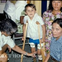 Image of Sr. Theo Mandragos, Physical Therapist, with patient and family.