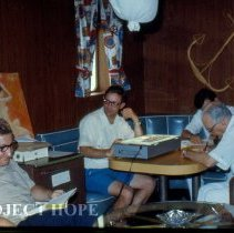 "Image of Gus Pappas, Ron Neafie, ?, ? in the ""Jungle"", doctors quarters"