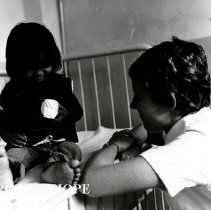 Image of Teri O'Brien de Brito, Pediatric nurse, with patient at Hospital Infantile