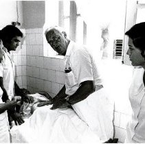 Image of James Hennessey examines a patient at Santa Casa Hospital, in Maceio