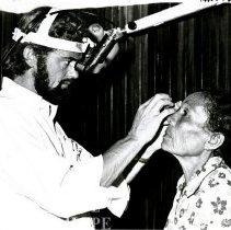 Image of Opthalmologist John S. Barker, MD, examines patient at Santa Casa Hosp.