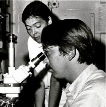 Image of Dr. Kenneth Brunner works at a microscope with Brazilian counterpart.