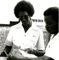 Image of Everlina Holmes, RRL works with her counterpart in medical records.