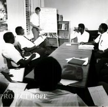 Image of Tom Kirby with Public Health Inspectors, showing a chart.