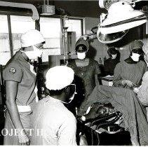 Image of Margot Barrett observes techniques of nurse anesthetist at major operation