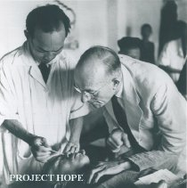 Image of HOPE Opthamologist and counterpart examine an Indonesian patient.
