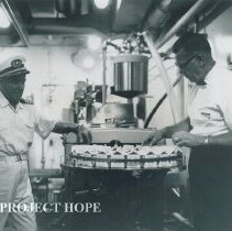 Image of SS HOPE Captain watches the Iron Cow make milk on Voyage III Ecuador.