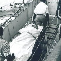 Image of Carrying a patient up the gangway in Jamaica Voyage IX.