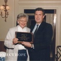 Image of Alumni - Dr. Jean Kohn president of Project HOPE Alumni Association receiving an award from Bill Walsh, Jr. for the Archives Project.