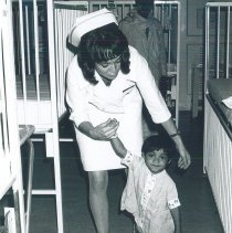 Image of Mary Carol Clark with child who learned to walk on the SS HOPE in Ceylon.