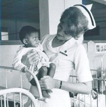 Image of Doris Beister holding a Pediatric patient on the SS HOPE in Ceylon.