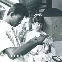 Image of Grace Tucker, a registered nurse intructing a Ceylonese Med Tech in Ceylon.