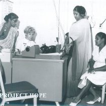 Image of Robin Radin and interpreters at Admissionsdesk on the SS HOPE in Ceylon.