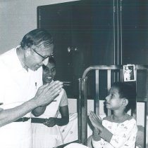 Image of Sam Kron with Dr Vedanayake and patient on the SS HOPE in Ceylon.