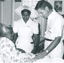 Image of Bruce Linderholm with nurse and patient on the SS HOPE in Ceylon.