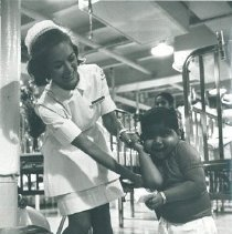 Image of Mary Lou Panter with Pediatric patient on the SS HOPE in Ceylon.