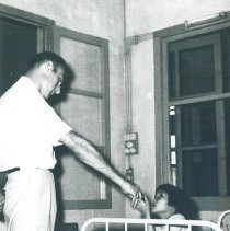 Image of An unknown HOPE doctor with a patient on the SS HOPE in Saigon, Viet Nam.