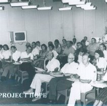 Image of William B Walsh (arms folded) in lecture on the SS HOPE in Saigon, Viet Nam