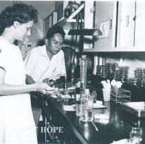 Image of Mary Jo Ann Crary with counterpart in laboratory on SS HOPE Indonesia. 1960