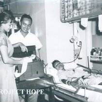 Image of Harriet Seipel doing electrocardiograph on SS HOPE in Indonesia 1960.