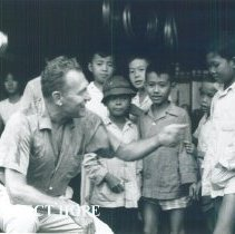Image of Ralph Bellamy chats with young Vietnamese while televising a documentary.