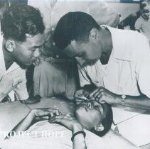 Image of Unknown HOPE doctor on left with counterpart and patient on SS HOPE 1960.