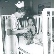 Image of Mary Finley with patient on the SS HOPE in Indonesia 1960