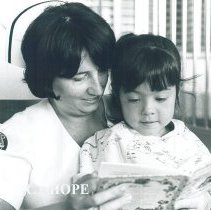Image of HOPE nurse Mary Payne reading to young patient in Mercy Hospital.