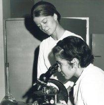 Image of HOPE Med Tech Mary Day teaching microscope technizue in Quito, Ecuador.