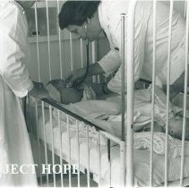 Image of Dr Terry King with 2 Polish patients in the same bed in Poland.