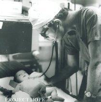 Image of Dr James Graham examines patient in Institute of Pediatrics Poland.