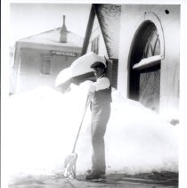 Image of Man with snow shovel in front of City Hall