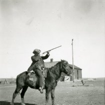 Image of Man on a horse pointing rifle to the sky