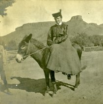 Image of Woman on burro with Castle Rock