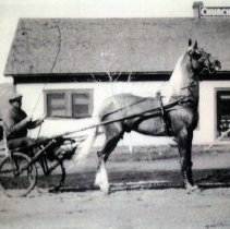 Image of Ralph Churches in a single seat horse-drawn carriage in front of Churches S