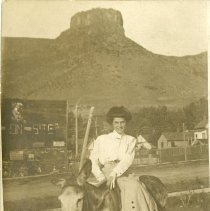 Image of 1910 picture postcard of a woman sitting sidesaddle on a mule