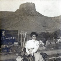 Image of 1910 picture postcard of a woman sitting sidesaddle on a mule, color correc