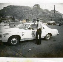 """Image of Edwin """"Erv"""" Noorlun next to Golden Police Department vehicle"""