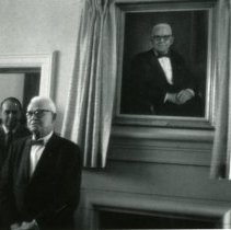 Image of Samuel A. Koenig next to a painting of himself