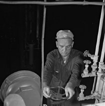Image of Worker operating a valve