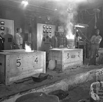 Image of Workers moving molten metal